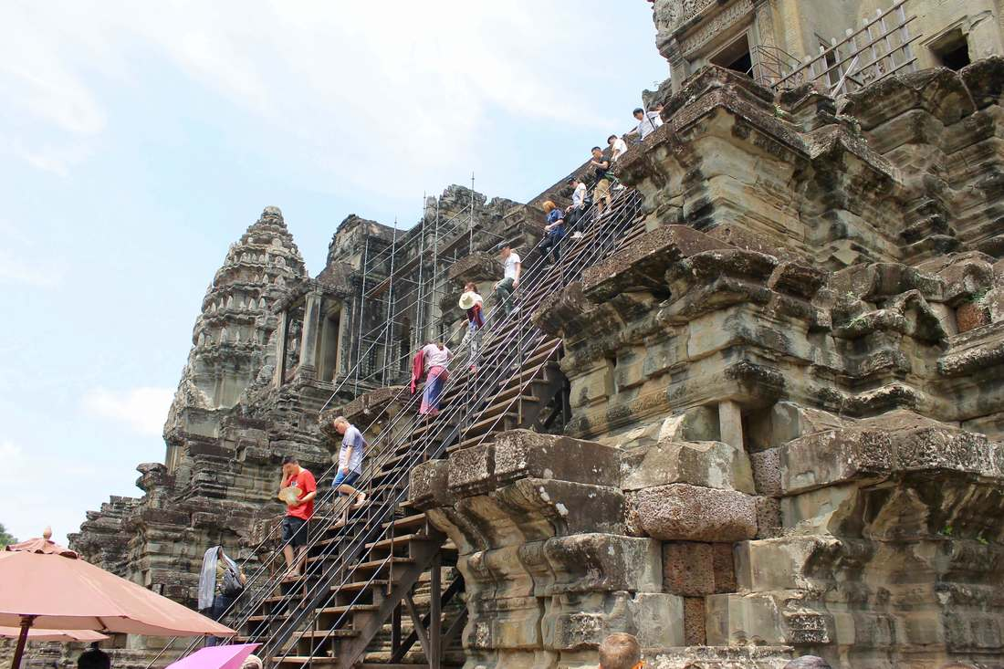 Visitors to Angkor Wat climbing steps to the top