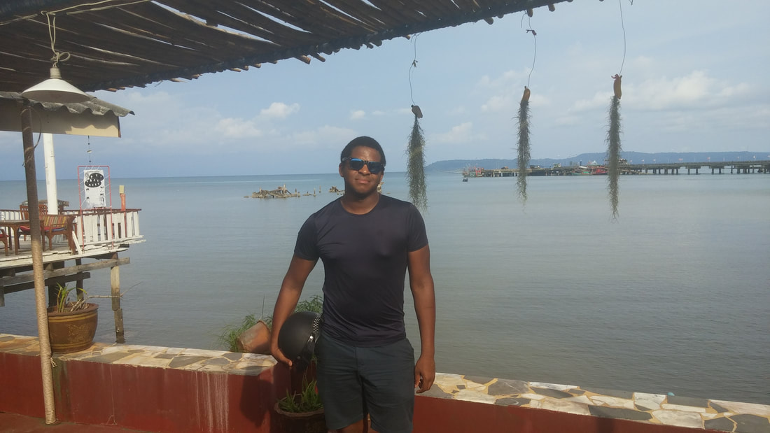 Picture of Blair at restaurant with beautiful water view behind him.